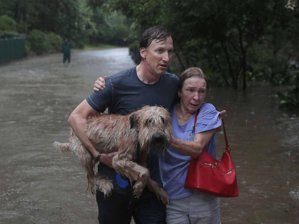 PHOTO: Andrew White (L) helps a neighbor down a street after rescuing her from her home in his boat in the upscale River Oaks neighborhood after it was inundated with flooding from Hurricane Harvey, Aug. 27, 2017, in Houston.