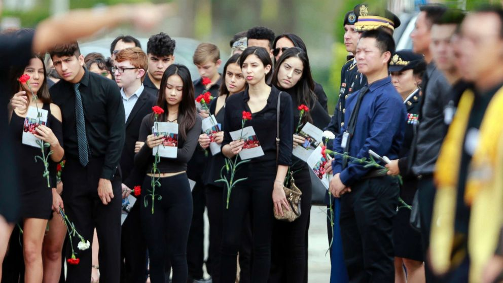 Mourners hold flowers during the funeral for Peter Wang at Kraeer Funeral Home in Parkland, Fla., on Feb. 20, 2018.