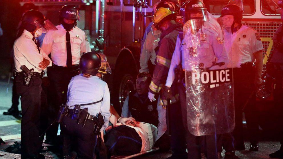 FOTO: Ein Polizist liegt am Boden, bevor er am 27. Oktober 2020 in einen Krankenwagen in der 52. Straße in West Philadelphia geladen wird.