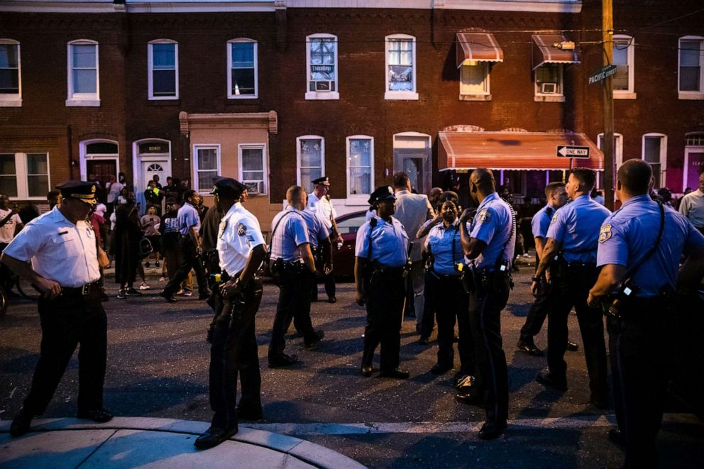 PHOTO: Officers gather for crowd control near a massive police presence set up outside a house as they investigate an active shooting situation, in Philadelphia, Aug. 14, 2019.