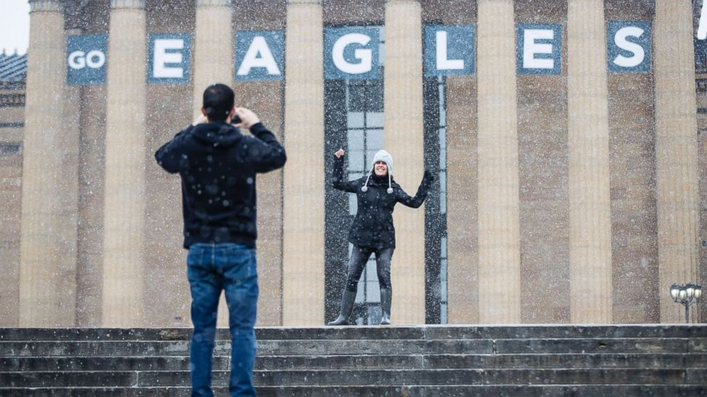 A woman poses for a photograph in view of a Philadelphia Eagles banner hung on the Philadelphia Museum of Art in Philadelphia, Penn., Jan. 30, 2018.