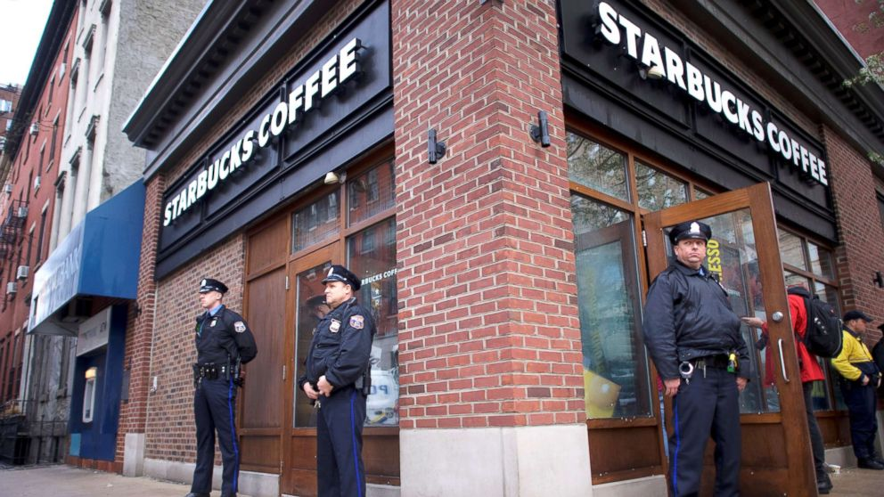 Police officers monitor activity outside as protesters demonstrate inside a Center City Starbucks, where two black men were arrested, in Philadelphia, April 16, 2018.