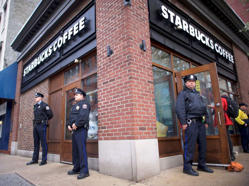 PHOTO: Police officers monitor activity outside as protestors demonstrate inside a Center City Starbucks, where two black men were arrested, in Philadelphia, April 16, 2018.