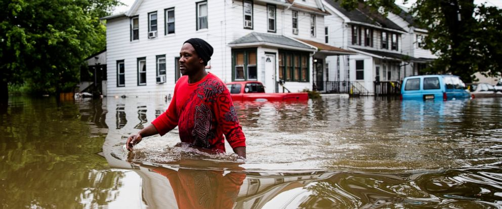 PHOTO: Chris Smith makes his way through floodwaters to the Macedonia Baptist Church in Westville, N.J., Thursday, June 20, 2019.