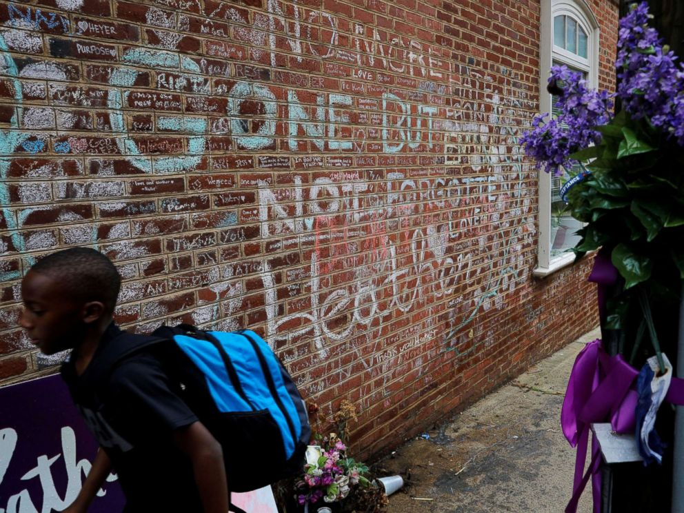 PHOTO: A boy passes tributes written at the site where Heather Heyer was killed during the 2017 white-nationalist rally in Charlottesville, Va., Aug. 1, 2018.