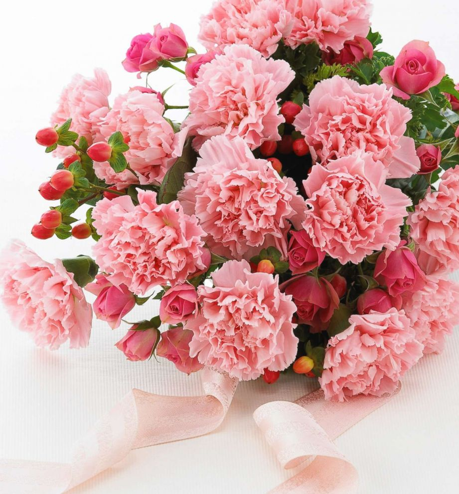 PHOTO: Bouquet of pink carnations sits on the table with a pink ribbon.