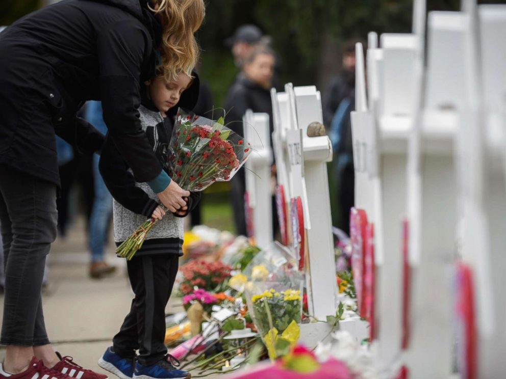 PHOTO: A mother and child place flowers, Oct. 29, 2018, at a memorial for victims of the mass shooting at the Tree Of Life Synagogue, in Pittsburgh.