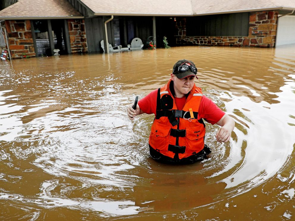 PHOTO: Tulsa County Sheriffs Deputy Miranda Munson makes her way back to a fan boat after checking a flooded house for occupants in the Town and Country neighborhood in Sand Springs, Okla., Thursday, May 23, 2019.