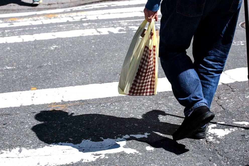 PHOTO:A man carries a plastic shopping bag as he walks Near Central Park in New York City, April 26, 2018.