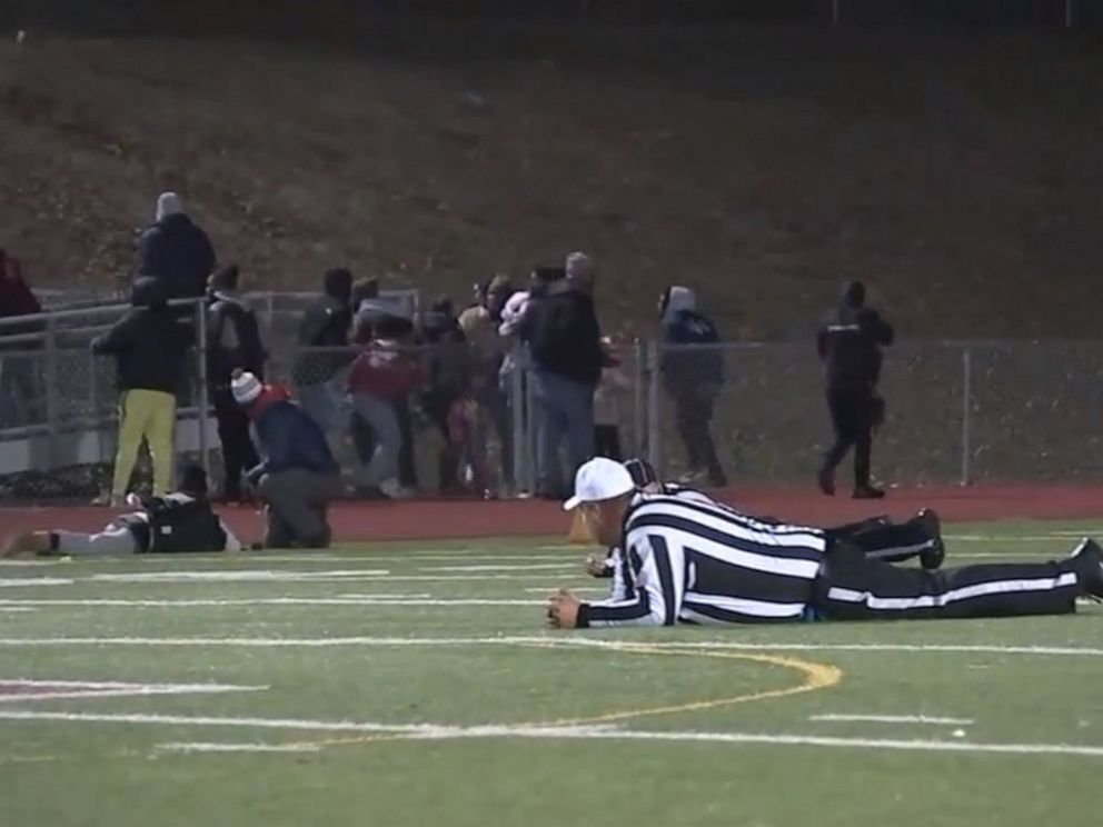 PHOTO: Referees and players take cover after shots were fired at a high school football game in Pleasantville, New Jersey, Nov. 15, 2019.