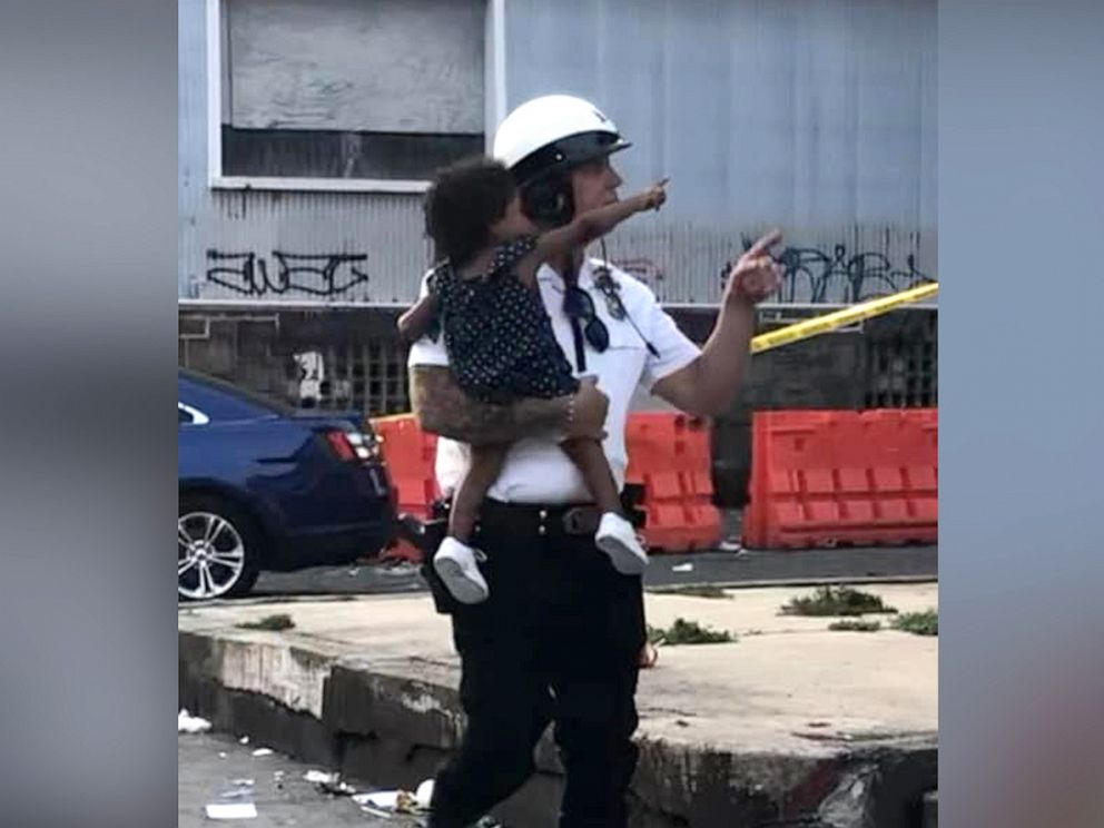 PHOTO: Sgt. Ed Pisarek, of The Philadelphia Highway Patrolm helping escort a baby from one of the daycare center during the shootout.