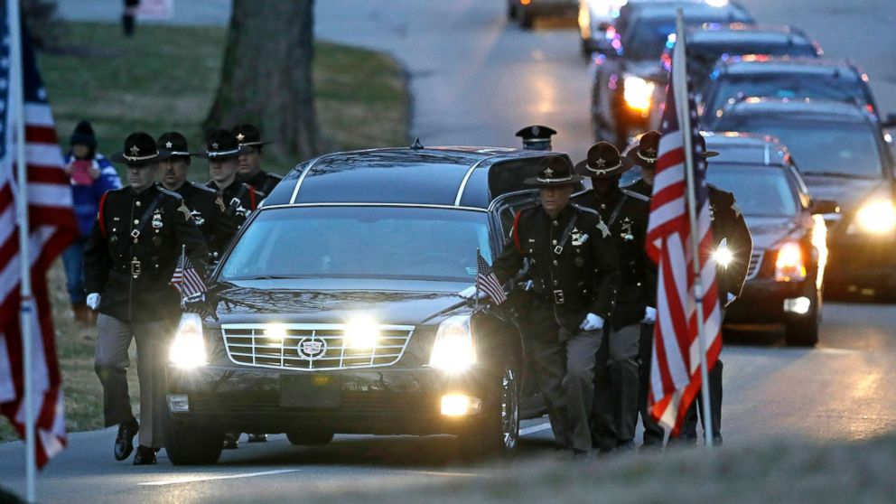 The honor guard walks along the hearse carrying the casket of Boone County Sheriff's Deputy Jacob Pickett, March 9, 2018, in Indianapolis. Pickett was fatally shot March 2, 2018, while chasing a man fleeing from police.