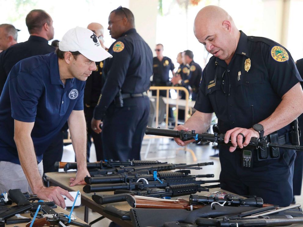 PHOTO: City of Miami Commissioner Ken Russell and City of Miami Police Officer Laurenceau look at some of the returned guns during a City of Miami gun buy-back event in Miami, March 17, 2018.