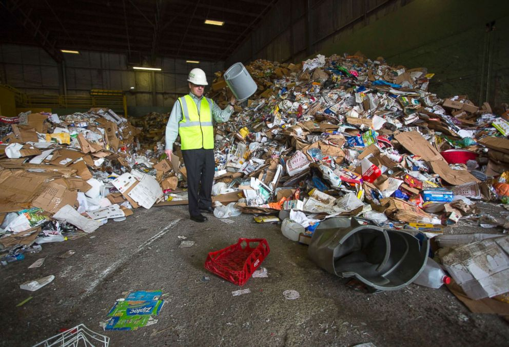 PHOTO: Ecomaine CEO Kevin Roche picks through unsorted materials after it was delivered to the facility in Portland, Maine, May 3, 2018.