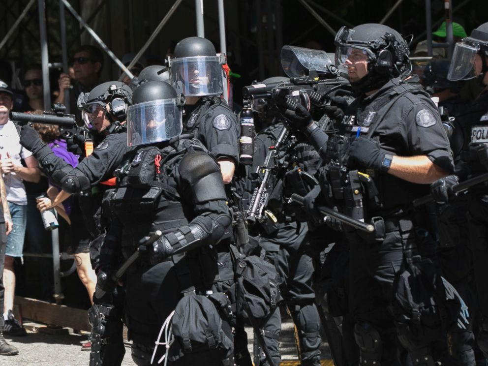 Police move in on protesters during a rally in Portland, Ore., Saturday, Aug. 4, 2018. Small scuffles broke out Saturday as police in Portland, Oregon, deployed flash bang devices to disperse hundreds of right-wing and anti-fascist protesters.