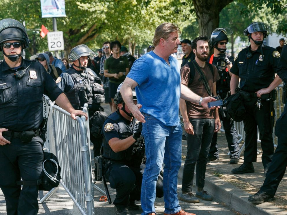 Police search a person before entering a rally in Portland, Ore., Saturday, Aug. 4, 2018.