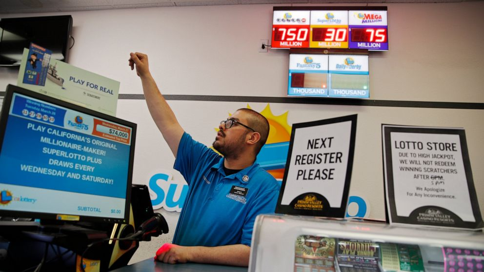 Cashier Edward Kelliher sells lottery tickets at the Lotto Store at Primm just inside the California border Wednesday, March 27, 2019, near Primm, Nev. The Powerball jackpot soared to a massive $750 million Wednesday.