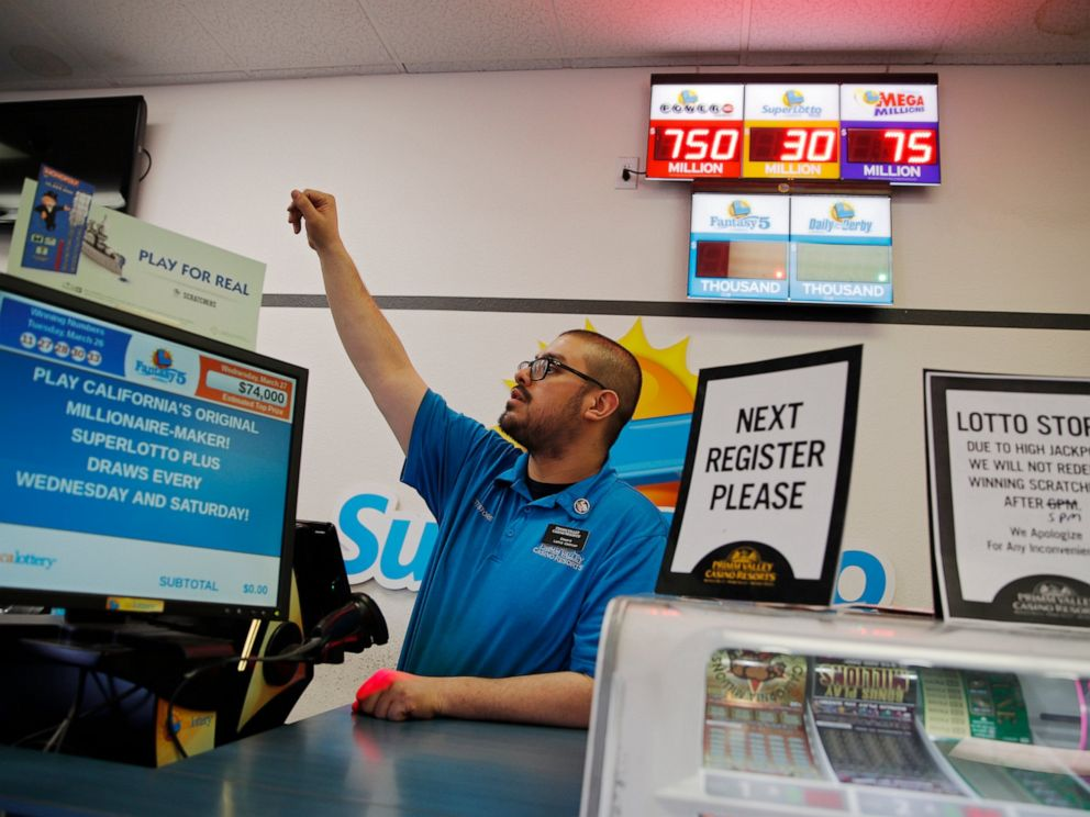 PHOTO: Cashier Edward Kelliher sells lottery tickets at the Lotto Store at Primm just inside the California border Wednesday, March 27, 2019, near Primm, Nev. The Powerball jackpot soared to a massive $750 million Wednesday.
