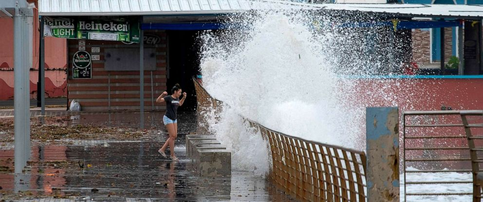 PHOTO: TOPSHOT - A woman waks next to the coast as tropical Storm Karen approaches in Naguabo, Puerto Rico, on September 24, 2019.