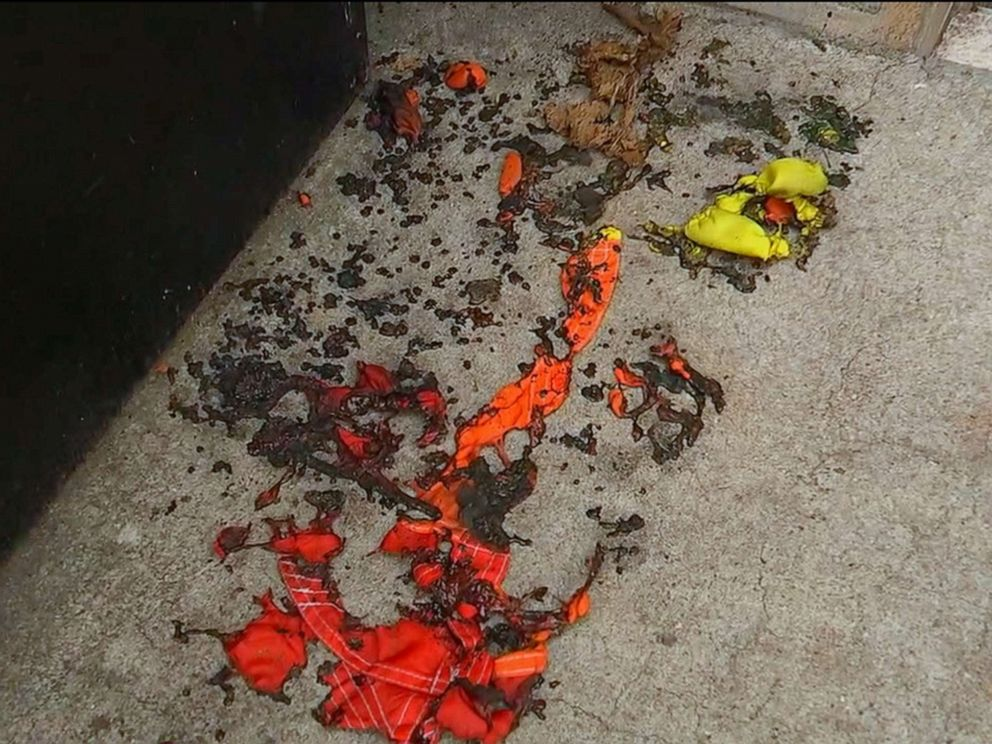 PHOTO: The charred remains of a rainbow pride flag sit on the ground outside the Alibi Lounge in the Harlem borough of New York after it was burned by a vandal, July 8, 2019.
