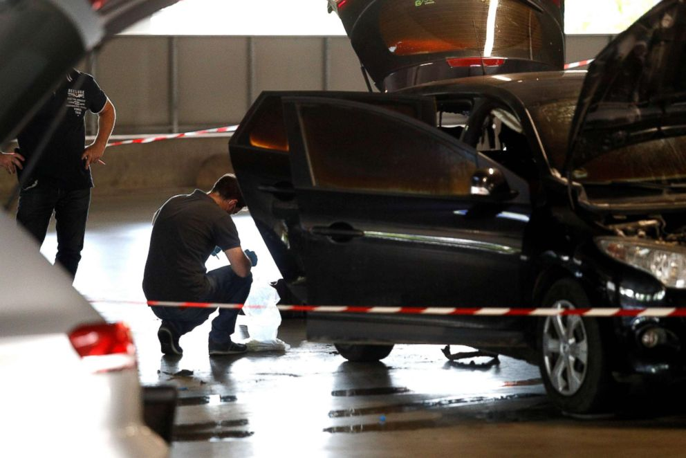 This picture taken on July 1, 2018 in Aulnay-sous-Bois, north of Paris, shows a forensic police officer investigating a car abandoned by French armed robber Redoine Faid at O'Parinor shopping mall parking after his escape onboard a helicopter from a prison in Reau.