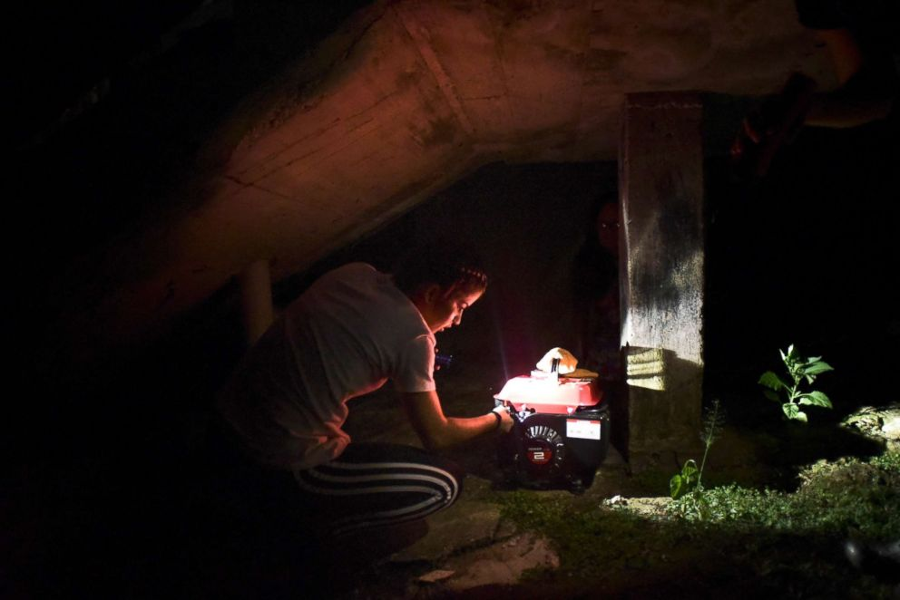 PHOTO: Resident Karina Santiago Gonzalez works on a small power plant in Morovis, Puerto Rico, Dec. 21, 2017.