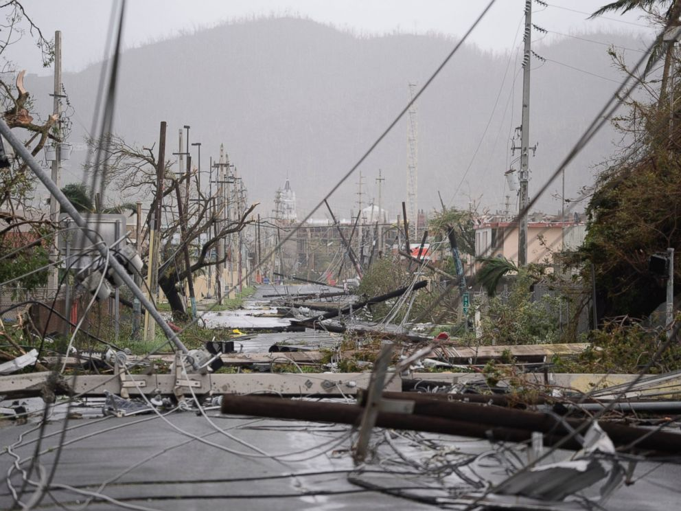 In this Sept. 20, 2017 file photo, electricity poles and lines lie toppled on the road after Hurricane Maria hit the eastern region of the island, in Humacao, Puerto Rico.