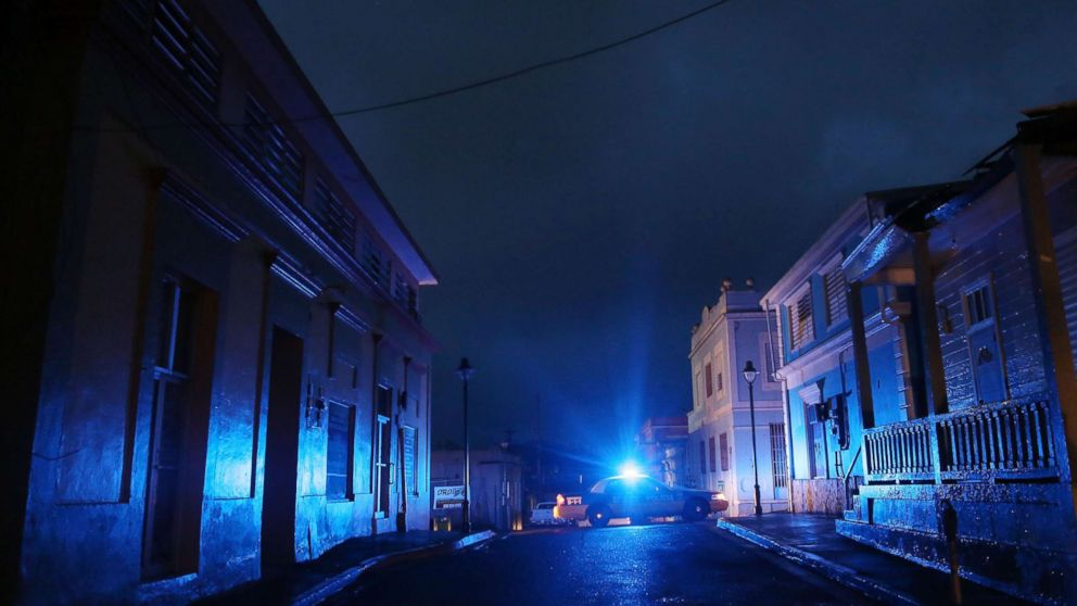 In this Oct. 11, 2017 file photo, A police car patrols on a darkened street three weeks after Hurricane Maria hit the island, in Aibonito, Puerto Rico.