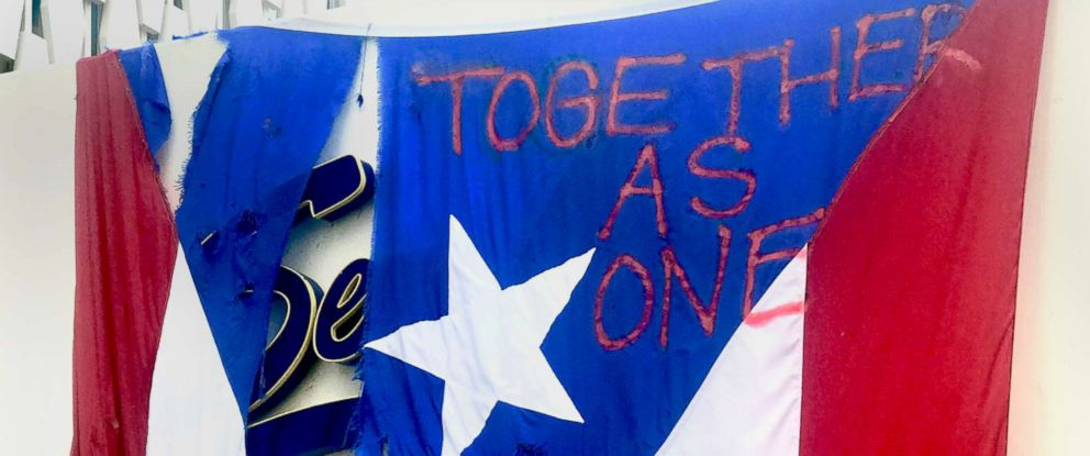 "PHOTO: A torn Puerto Rico flad with the words ""Together as one"" written on it, hangs outside a restaurant in San Juan, Oct. 5, 2017."