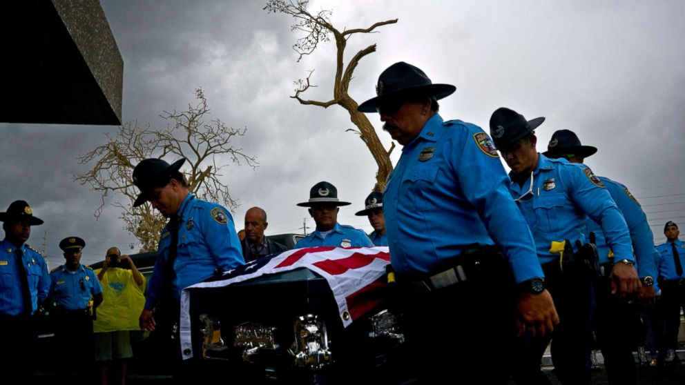 Honor guards carry the coffin of policeman Luis Angel Gonzalez Lorenzo, killed during Hurricane Maria when he tried to cross a river by car, during his funeral at the cemetery in Aguada, Puerto Rico, Sept. 29, 2017.