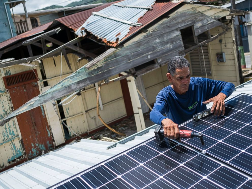 In this July 24, 2018 photo, Julio Rosario installs a solar energy system at a home in Adjuntas, Puerto Rico.