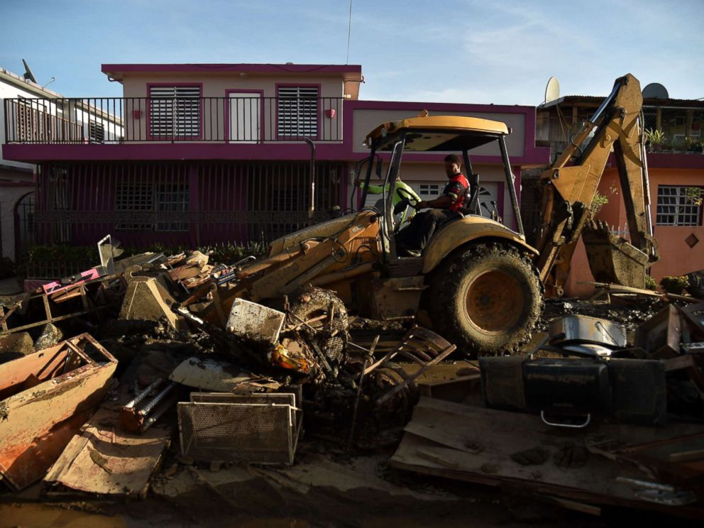 PHOTO: A man bulldozes furniture damaged and debris following Hurricane Maria on a street in Toa Baja, Puerto Rico, Sept. 25, 2017.