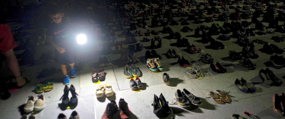PHOTO: A child shines a light on hundreds of shoes at a memorial for those killed by Hurricane Maria, in front of the Puerto Rico Capitol in San Juan, June 1, 2018.
