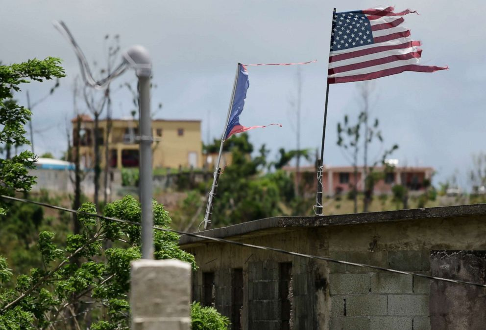 PHOTO: Deteriorated U.S. and Puerto Rico flags fly on a roof eight months after the passing of Hurricane Maria in the Barrio Jacana Piedra Blanca area of Yabucoa, May 16, 2018.