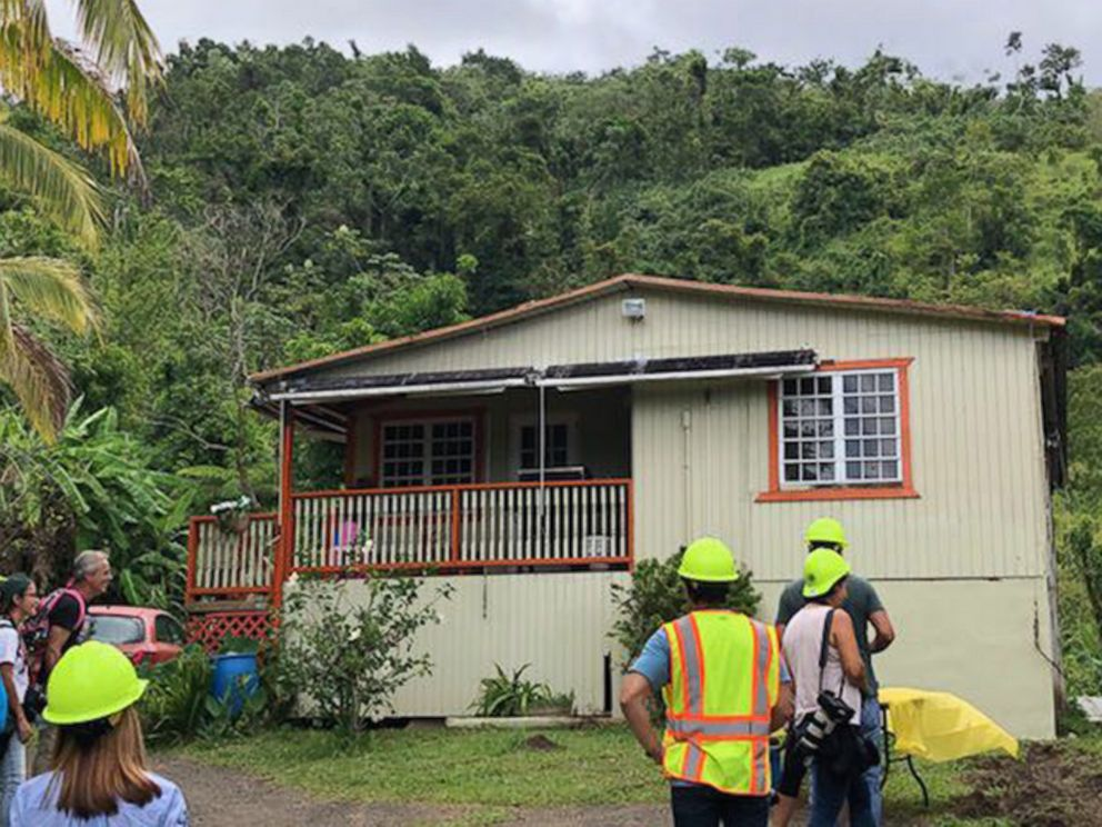PHOTO: Workers stand outside one of the two homes that had power restored on Aug. 14, 2018, after a mission by the Puerto Rico Electric Power Authority in Ponce.