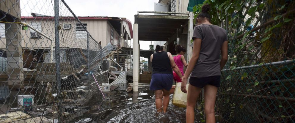 PHOTO: Residents wade through a flooded area in the aftermath of Hurricane Maria, in Catano, Puerto Rico, Sept. 27, 2017.