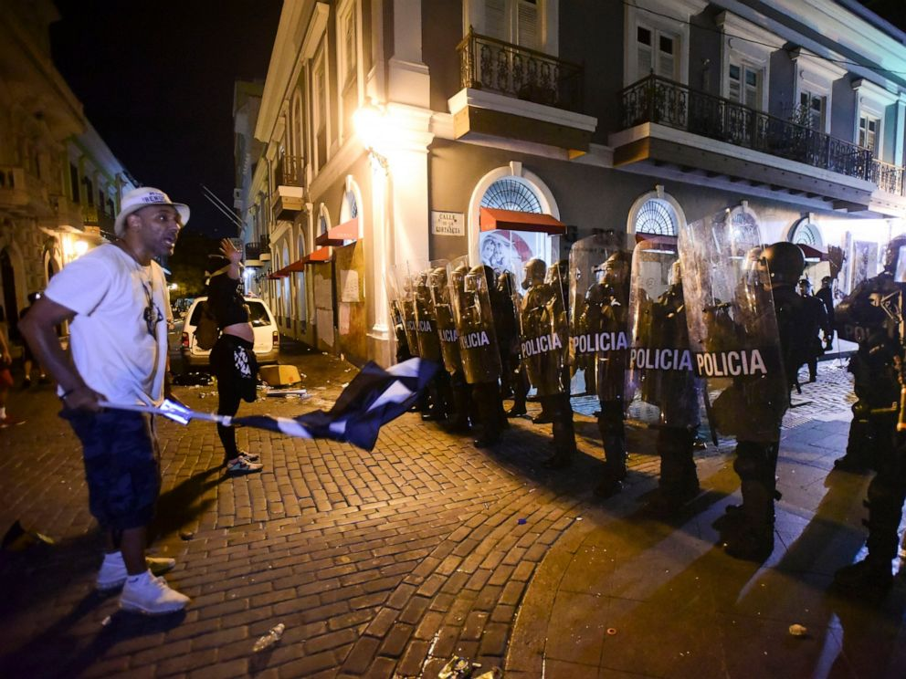 PHOTO: Demonstrators stand in front of riot control units during clashes in San Juan, Puerto Rico, Monday, July 22, 2019. Protesters are demanding Gov. Ricardo Rossello step down following the leak of an offensive, obscenity-laden online chat.