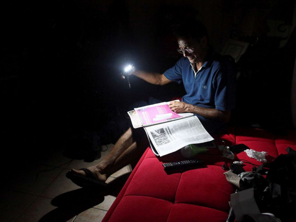 PHOTO: Hugo Regalado reads the newspaper with the help of a flashlight months after Hurricane Maria damaged the electrical grid in Dorado, Puerto Rico, Jan. 15, 2018.