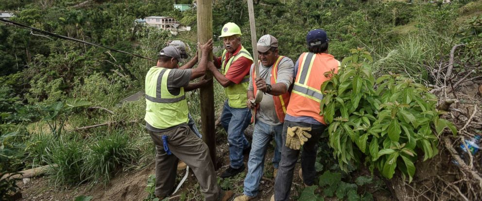 PHOTO: Public Works Sub-Director Ramon Mendez, wearing hard hat, directs locals who are municipal workers, as they install a power pole in an effort to return electricity to a home, in Coamo, Puerto Rico, Jan. 31, 2018.