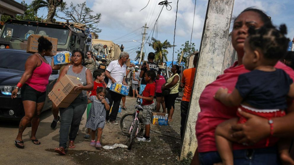 Residents gather to receive food and water from FEMA in a neighborhood without grid electricity or running water on Oct. 17, 2017 in San Isidro, Puerto Rico.