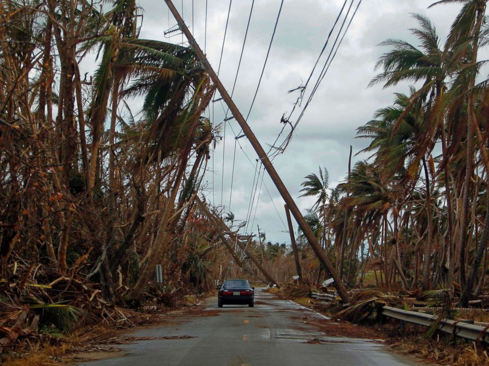 PHOTO: A car drives under tilted power line poles in the aftermath of Hurricane Maria in Humacao, Puerto Rico, Oct. 2, 2017.