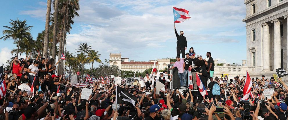 PHOTO: Rapper Bad Bunny (holding flag) singer, Ricky Martin (black hat) and Rapper Residente (blue hat) join demonstrators protesting against Ricardo Rossello, the Governor of Puerto Rico July 17, 2019, in Old San Juan, Puerto Rico.