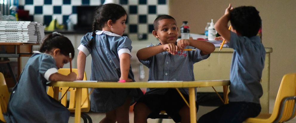In this Oct. 13, 2017 file photo, children discuss their thoughts about Hurricane Maria at Ramon Marin Sola Elementary School in Guaynabo, Puerto Rico.