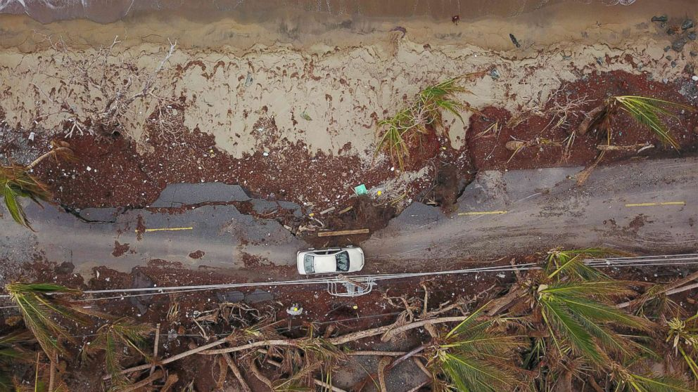 A car drives on a damaged road in the aftermath of Hurricane Maria in Humacao, Puerto Rico on Oct. 2, 2017.