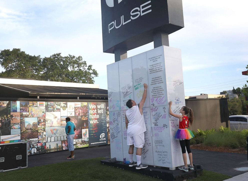 PHOTO: Jim McDermott (L) and Isabella Andriolo, 11, write messages on the Pulse sign as they visit the memorial to the 49 shooting victims setup at the Pulse nightclub where the shootings took place two years ago, June 12, 2018, in Orlando, Fla.