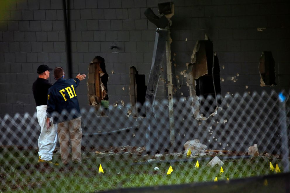 PHOTO: FBI agents investigate near the damaged rear wall of the Pulse Nightclub, June 12, 2016, in Orlando, Fla.