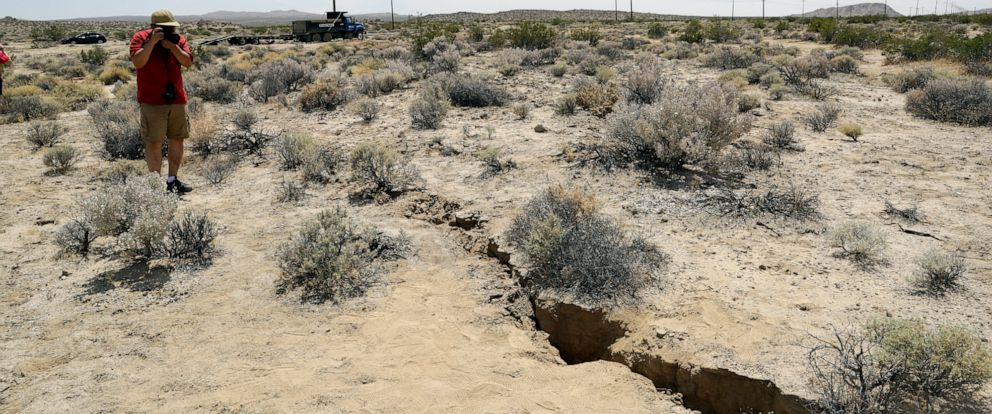 PHOTO:A visitor takes a photo of a crack on the ground following recent earthquakes, July 7, 2019, outside of Ridgecrest, Calif.