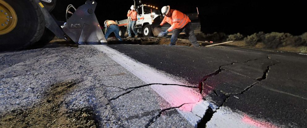 PHOTO: Highway workers repair a hole that opened in the road as a result of an earthquake, near Ridgecrest, Calif., early in the morning on July 6, 2019.