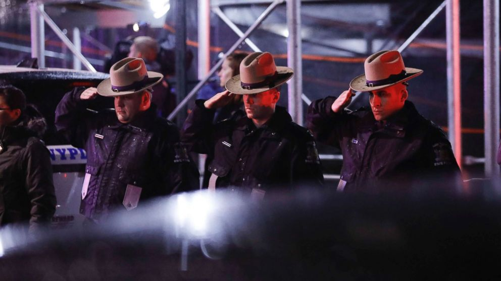 Officers salute a procession as the remains of slain Detective Brian Simonsen are removed from Jamaica Hospital, Feb. 12, 2019, in the Queens borough of N.Y.