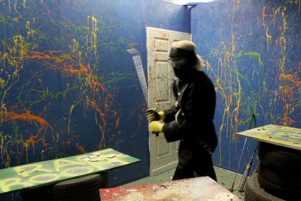 PHOTO: Participants take part in a rage room to release tension and stress.
